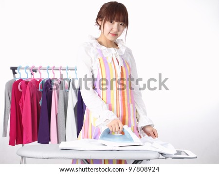 A Chinese woman is using a electric iron with many clothing. - stock photo
