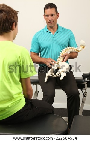 A Chiropractor showing a model of the human spine to a boy - stock photo