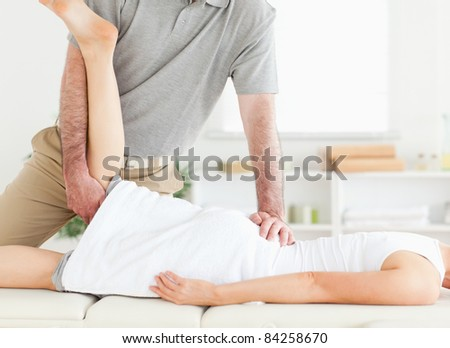 A chiropractor stretches a woman's leg in his surgery