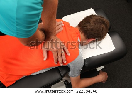 A Chiropractor treating a young boy - stock photo