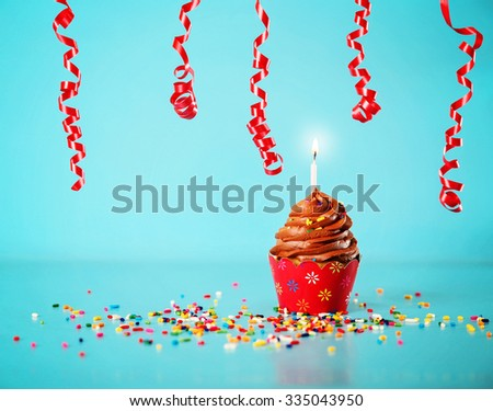a chocolate birthday cupcake with a red paper skirt and streamers and a lit candle and sprinkles on a blue background - stock photo