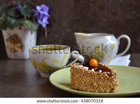 A chocolate cake decorated with kumquat, caramel fondant, chocolate wave,hazelnut frosting  and drops of white whipped cream. Dessert and  porcelain cup of green tea. Selective focus. - stock photo