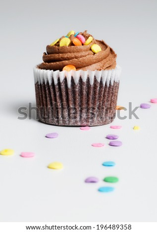 A chocolate cupcake with chocolate icing and sprinkles. - stock photo
