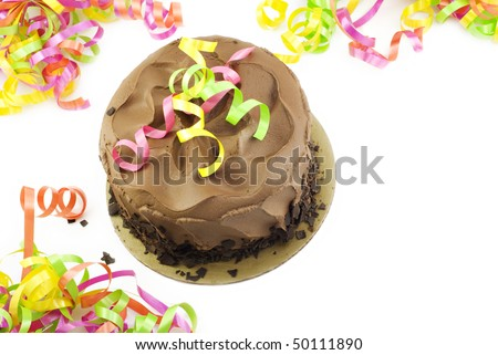 A chocolate fudge layer cake with colorful party ribbons on a white horizontal background with copy space, top view - stock photo