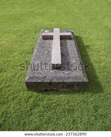A Christian cross symbol on a tombstone or grave stone on a neatly cut grass lawn - stock photo