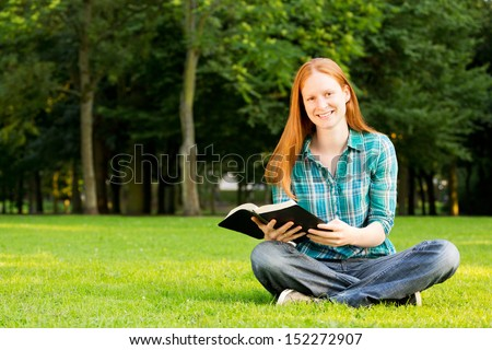 A Christian woman holding a Bible and smiling at the camera, photographed in a public park.