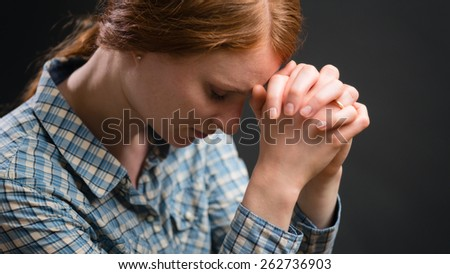 A Christian woman prays to God with head resting on her hands. Closeup portrait under dramatic light.