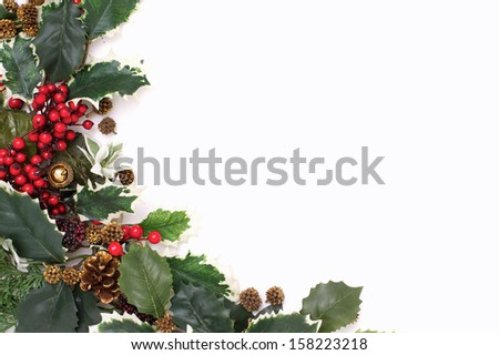 A christmas arrangement of green leaves and red berries - copy space - stock photo