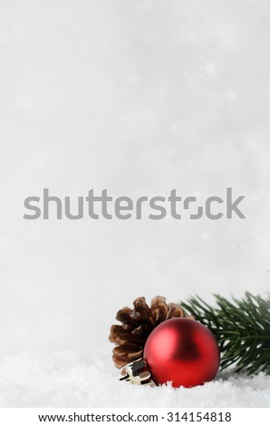 A Christmas border and background with red bauble, fir cone and green branch, nestling in white fake snow in lower right corner.  Twinkling stars in background. - stock photo