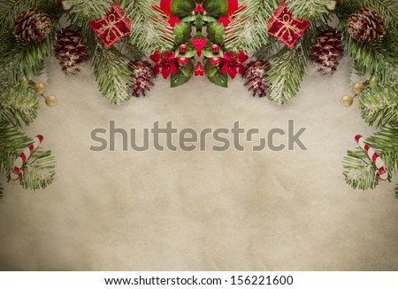 A Christmas border at top of frame consisting of artificial pine tree fronds and decorative ornaments, framing top and sides of grungy parchment. - stock photo