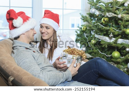 A Christmas Couple wearing Santa's Hats. Smiling Family Celebrating New Year at Home