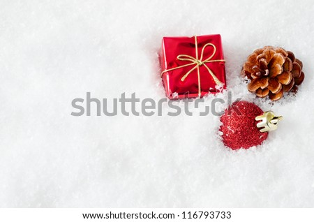 A christmas gift box, bauble and fir cone, embedded in fake white snow to the right of frame, with copy space on the left.