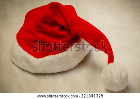 A Christmas Santa hat in vintage style on  parchment like paper. - stock photo