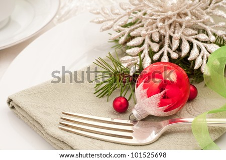A Christmas Table Setting closeup with a Vintage Ornament for Breakfast, Lunch, Brunch, Supper or Dinner and to be used as an invitation or card for a holiday get together with copy space. - stock photo