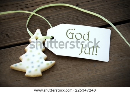 A Christmas Tree Cookie with a Label with the swedish or norwegian Words God Jul on it which means Merry Christmas - stock photo