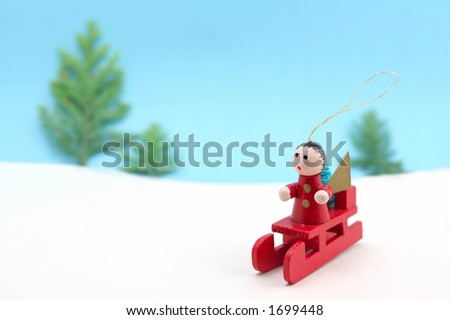 A Christmas tree decoration sets off across a snowy landscape on a sledge - stock photo