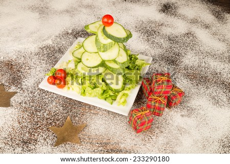 A Christmas tree salad made with cucumber and cherry tomatoes, a  healthy kid meal - stock photo
