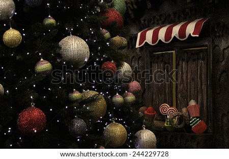 A Christmas tree with glittery baubles near various fake cupcakes, candy, doughnuts, and ice cream cones decoration on wooden window ledge.  - stock photo