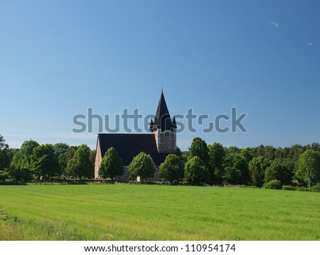 A church building in the field on a sunny day - stock photo