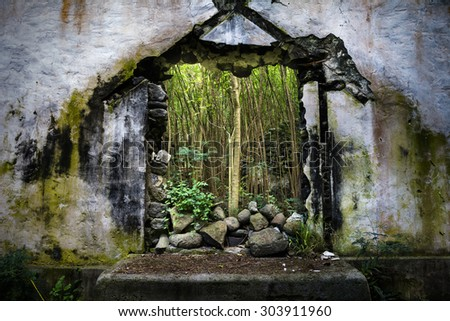 A church in Molokai Hawaii that was destroyed by a tsunami in the 1940s remains partially standing, with jungle now growing through the middle. - stock photo