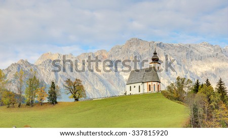 A church standing high on grassy hilltop with a rugged mountain range in the background ~ Magnificent autumn scenery of Parish Church St. Nikolaus of Dienten and Hochkoenig Mountains in Austria - stock photo