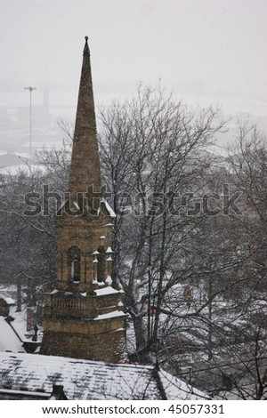 A church steeple during a snowstorm