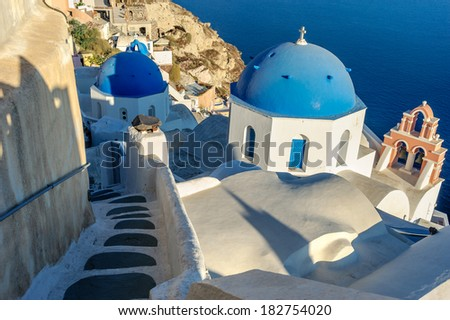 A church with a blue dome overlooks the spectacular caldera surrounding the beautiful island of Santorini, Greece - stock photo