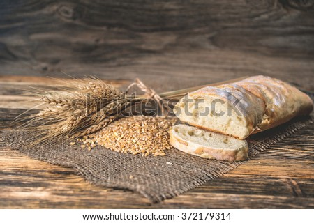 a ciabatta bread with wheat on stackcloth on a wooden rustic background