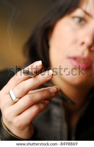 A cigarette in a hand of dark hair woman