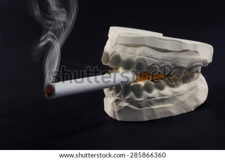A cigarette in his mouth that harms the health of our teeth - stock photo