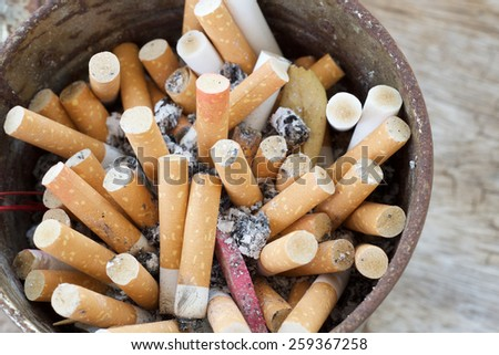 A cigarette with ash end rests on the side of a nearly full and dirty ashtray - stock photo