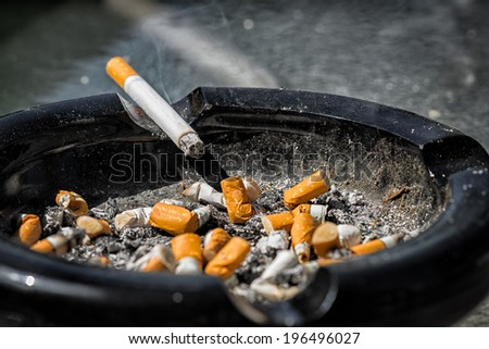 A cigarette with ash end rests on the side of a nearly full and dirty ashtray containing much ash and many crushed cigarette butts.
