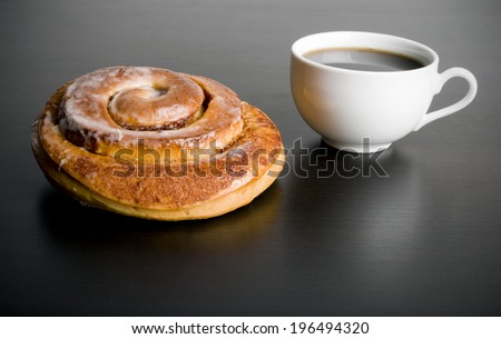A cinnamon bun and coffee on a black surface.