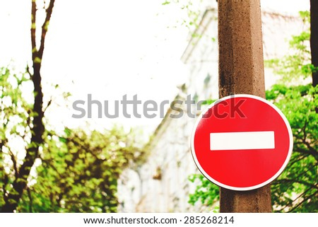 A circular red sign with a white bar indicating 'NO ENTRY' on a wooden post against a building and sky - stock photo