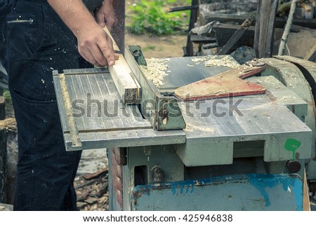 A circular saw, workplace, work profession, woodworking machine, wood cutting, building a house,  green bushes on background, construction, industrial, experience - stock photo