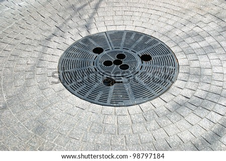 A circular water drain on a sunny day - stock photo