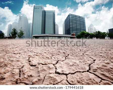 A city looks over a cracked earth landscape - stock photo