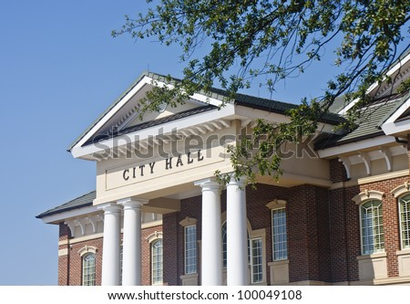 A classic brick town city hall through the trees - stock photo