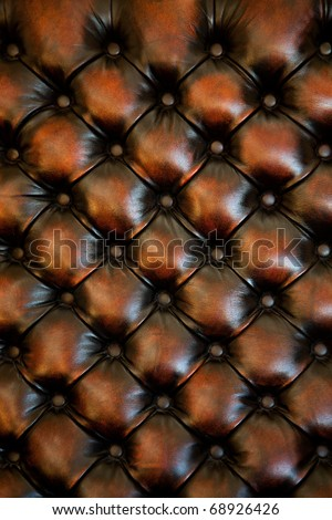 A classic brown leather and button upholstery on a chair back. - stock photo