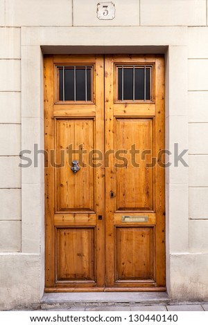 A classic double wooden door with a knocker and two little grilled windows on the upper part. The picture has been taken in the Sarri�  quarter of Barcelona, where old wooden doors are still typical. - stock photo