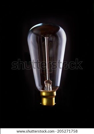 A classic Edison light bulb with a squirrel cage filament. Switched Off. - stock photo