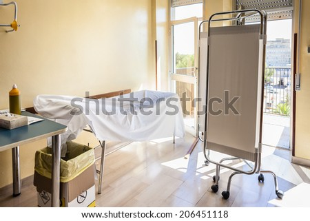 a classic examination room with a bed and a folding shield - stock photo