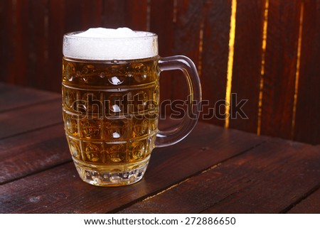 A classic mug full of light beer standing on a wooden table