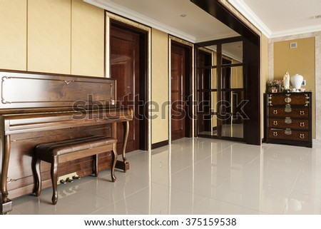 A classic(old, vintage) wood(walnut, teak) piano in a gold and cherry wood, marble bottom interior(living room, lounge)
