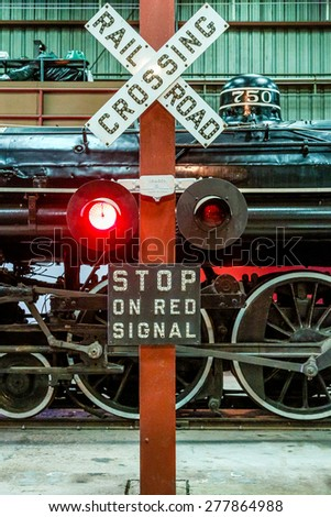 A classic Railroad Crossing sign and Old Locomotive - stock photo