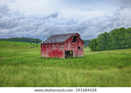 A classic red barn stands along in the grassy hills of a farm in Eastern Ohio. - stock photo