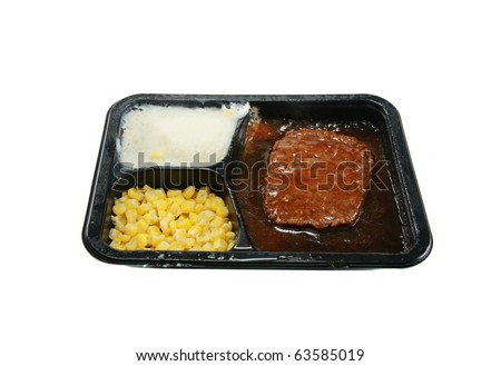 a classic salisbury steak tv dinner with mashed potatoes and corn in its black plastic tray, isolated on white - stock photo