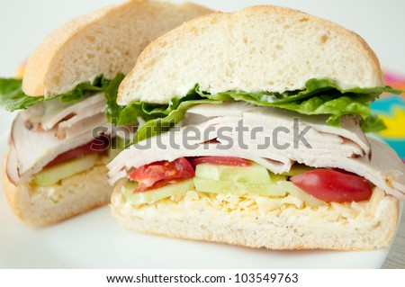 a classic turkey sandwich on a calabrese roll with tomato, lettuce, cheese, cucumber and mayonnaise. A lunchtime favorite