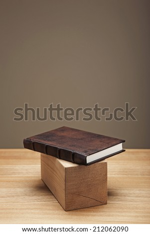 A classical brown diary with wood object on the desk. - stock photo