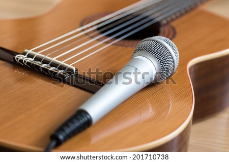A classical guitar with six nylon strings and microphone - stock photo